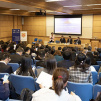 Audience and presenters at forum
